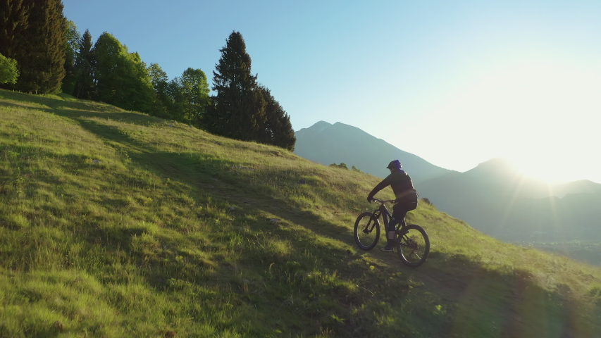 Drone is flying along an athletic man pedalling an MTB E-bike up a steep grassy hill. Beautiful view of the mountains at sunrise/sunset with sun flare. Alone in nature, thinking about life. | Shutterstock HD Video #1052869115