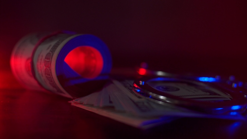 Police flasher. Handcuffs are on the table, a lot of money. They are lit by a flashing light glowing red and blue. | Shutterstock HD Video #1052870585