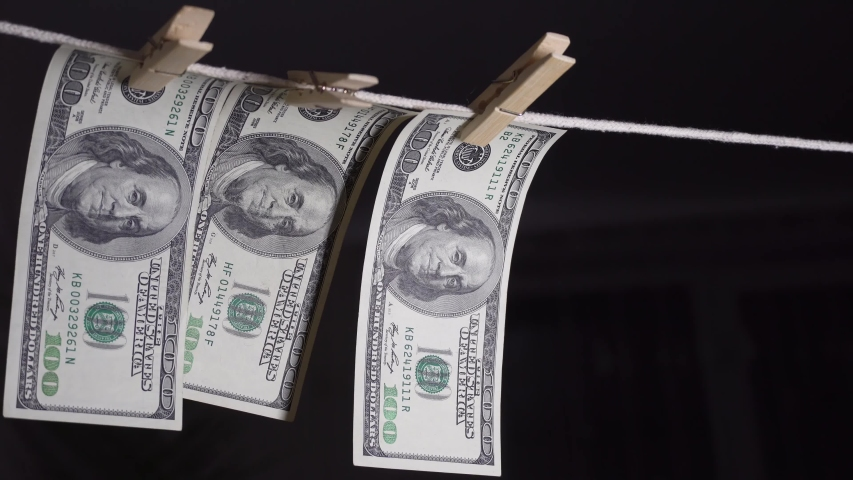 Dollars dry on a clothespin rope. The financial concept of the dollar. Hundred dollar bill on a rope. Money laundering concept. | Shutterstock HD Video #1052870687