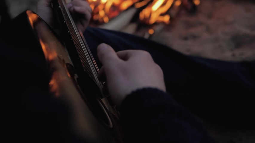 Men's hands play the guitar against a background of fire that burns in the sand. The view from the back. Summer evening .Slow motion | Shutterstock HD Video #1052874887