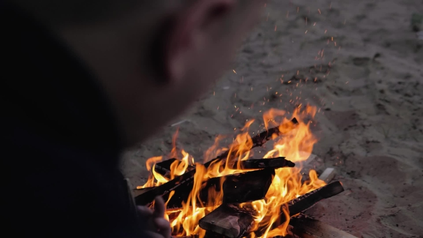 A man looks at the fire that burns in the sand. The view from the back. Summer evening.Slow motion. | Shutterstock HD Video #1052874893