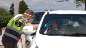 4K: Coronavirus COVID-19 Outdoor Testing station - A Woman has her temperature taken by army soldier - Mouth and Nose Swabs in her car. Stock Video Clip Footage