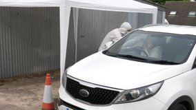 4K: Coronavirus COVID-19 Outdoor Testing Gazebo - A Woman has her temperature taken by a medic - Mouth and Nose Swabs in her car. Stock Video Clip Footage