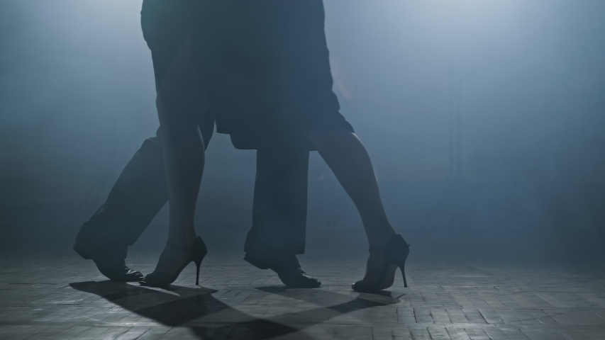 Beautiful man and woman dancing latin dance. Close-up of legs dancing tango in smoky studio in slow motion. 4K, UHD