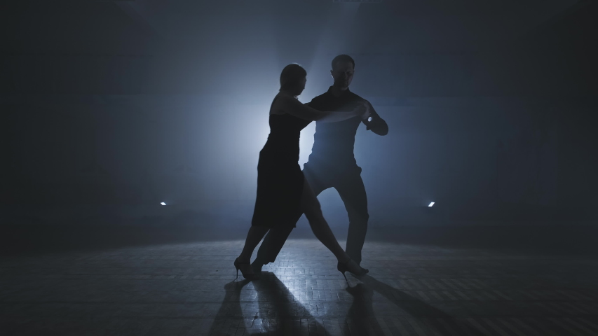 Silhouette of dancers in smoky ballroom. Young couple dance tango in dark room with smoke and spotlights in slow motion. Wide angle in 4K, UHD