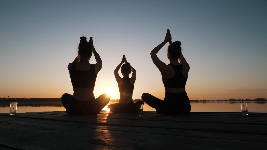 Silhouette of Diverse Group of Three Female Doing Yoga Awe Exercise Sitting in Lotus Position Together on Boardwalk Near Calm Water at Dusks Outdoor. Tranquil Namaste for Emotional Relief, Stress Free Royalty-Free Stock Footage #1052880119