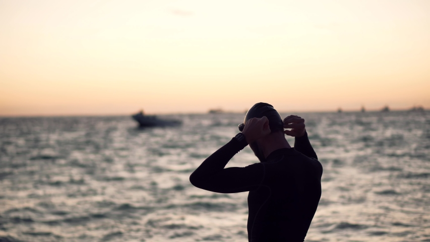 Professional Triathlete Prepare To Swimming Workout On Sea.Professional Swimmer Wearing Cup And Goggles.Triathlete Preparing To Triathlon Swim.Swimmer Silhouette In Ocean Sport Recreation Competition. Royalty-Free Stock Footage #1052887013