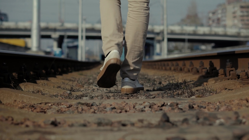Man Walks To Home On Railroad Tracks After Canceled Public Transport.Lonely Businessman Feet In Pants Walking On Rail Road When Train Or Tram Cancelled.Tourist Legs Walking On Railway Middle Of Rail.   Shutterstock HD Video #1052887598