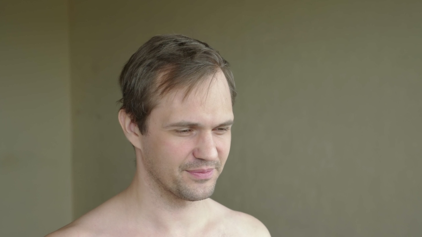 At home, a man shaves his bald spot in front of a mirror. hair loss problem. | Shutterstock HD Video #1052890397