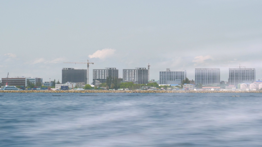 Unsightly business towers under construction tarnish the once beautiful coastline of an exotic island in the Maldives. Sailing past the developing shoreline of Male full of ugly high-rise buildings.   Shutterstock HD Video #1052892077