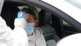 4K: Coronavirus COVID-19 Outdoor Testing station - A Woman has her temperature taken by her car window. - Mouth and Nose Swabs. Stock Video Clip Footage