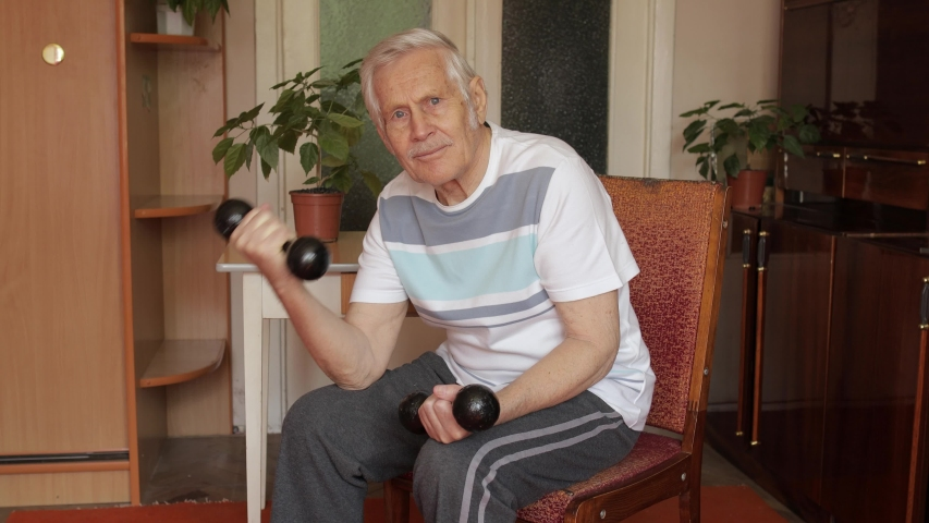 Senior elderly caucasian man in sportswear sitting on chair in living room, doing weight lifting dumbbell exercising at home. Active old retiree exercising in the morning. Leisure healthy lifestyle | Shutterstock HD Video #1052892671