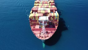 Aerial drone video flight over huge container cargo ship cruising the Mediterranean deep blue sea