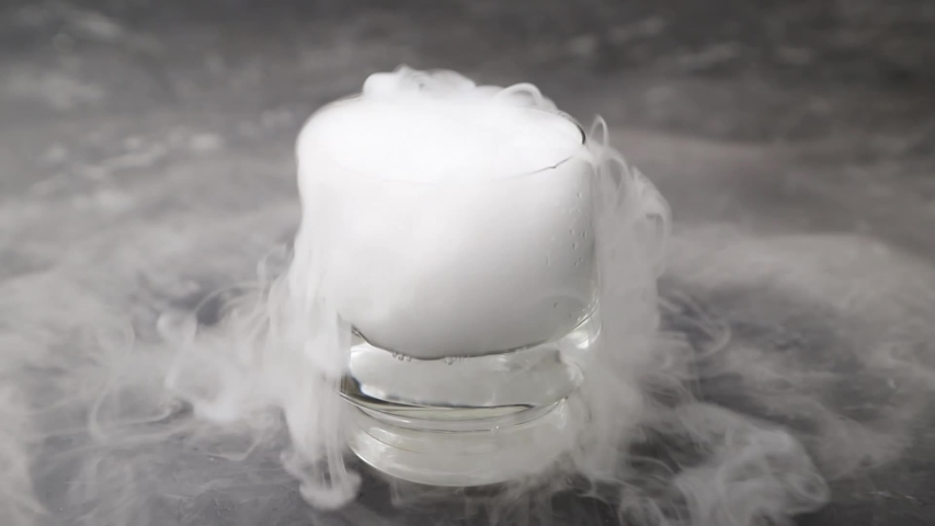 Dry ice fog flow from the transparent drinking glass on black concrete background. Chemical reaction with water. Side view, close up. | Shutterstock HD Video #1052897291