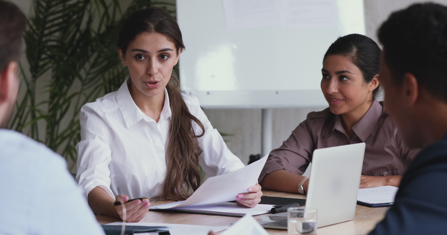 Beautiful millennial businesswoman holding paper marketing research reports, discussing growth strategy with diverse teammates. Motivated employees brainstorming on project, sharing ideas in office. Royalty-Free Stock Footage #1052897486