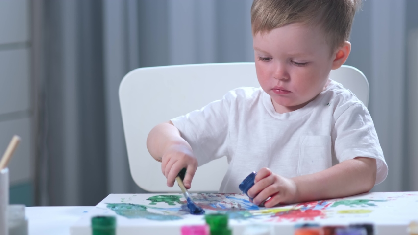 Fair-haired Caucasian artist child in white t-shirt with dirty, stained hands in paint sits at table in children's room and draws picture with brush with blue paint. Boy painter is engaged in art. | Shutterstock HD Video #1052897774
