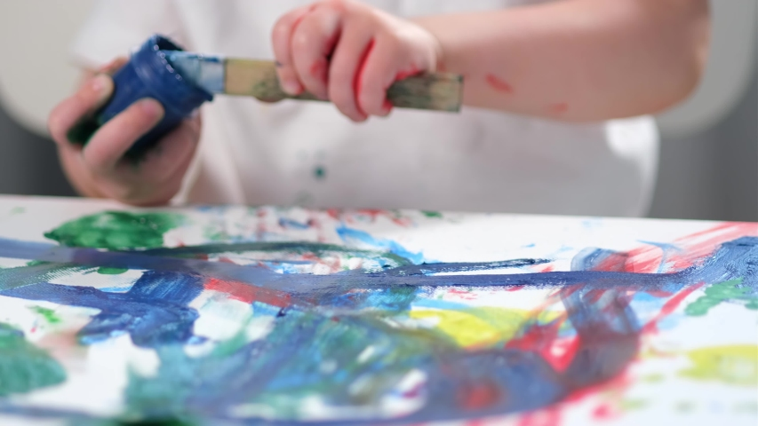 Сhild boy artist painter with stained hands in paint smears a brush in blue gouache paint with jar, leaves careless tools for drawing on painted picture and goes to wash his hands. | Shutterstock HD Video #1052897780