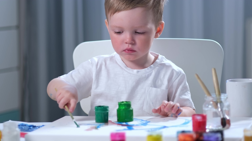 Cute fair-haired Caucasian artist child in white t-shirt with dirty, paint-stained hands, sits at table in children's room and draws picture with brush with green paint. Boy painter is engaged in art. | Shutterstock HD Video #1052897783