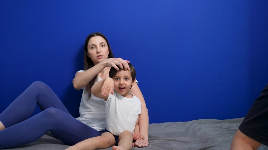 Family of three mom mom dad son sit on the bed against a blue wall | Shutterstock HD Video #1052897924