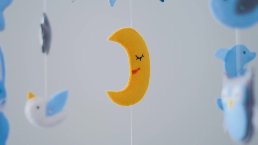 Baby mobile with different animals hanging over the crib of a newborn baby in the bedroom on a white background