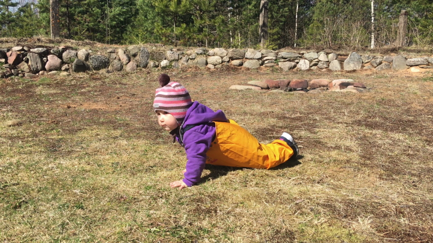 Caucasian toddler boy crawling on meadow in house backyard, wearing yellow trousers from waterproof and dirt-resistant material | Shutterstock HD Video #1052898743