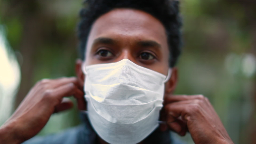 African man removing covid-19 mask, end of pandemic. Black person removes disease mask
