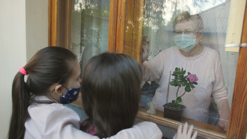 Visit of granddaughters to their grandmother during the coronavirus pandemic. Communication through the window.