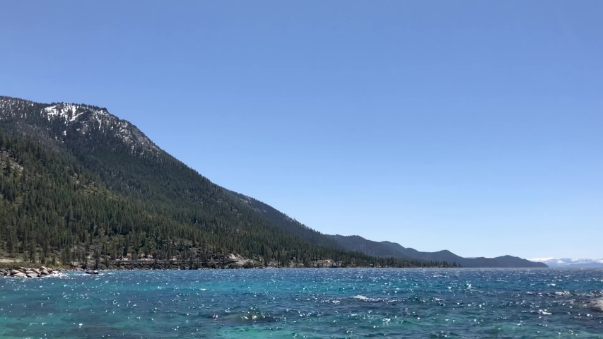 Beautiful mountains flowing into Lake Tahoe's clear blue water.