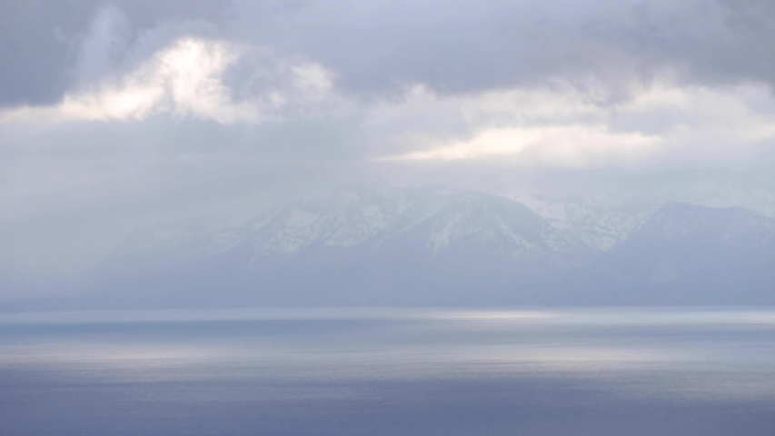 Beautiful shot of clouds rolling over Lake Tahoe with snow covered peaks in the background.