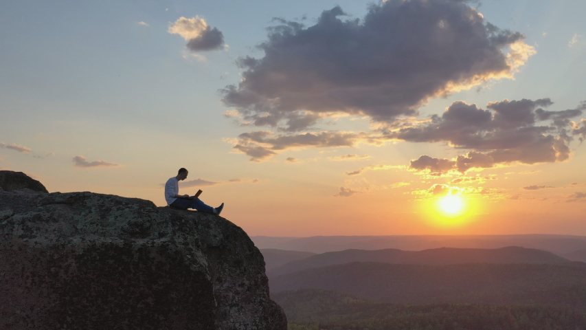 Aerial view of a young male freelancer working on a laptop sitting on a rock ledge in the mountains at sunset. | Shutterstock HD Video #1052907107