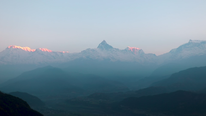 Snow Peak of Machapuchare Mountain also called Fishtail Mountain at Sunrise in the Himalayas in Nepal. selective focus  | Shutterstock HD Video #1052911583
