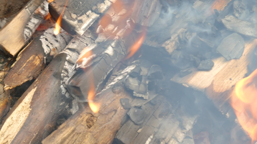 Burning coals at close range. A burning fire and black remnants of firewood. Thick smoke coming from the fire. | Shutterstock HD Video #1052913743