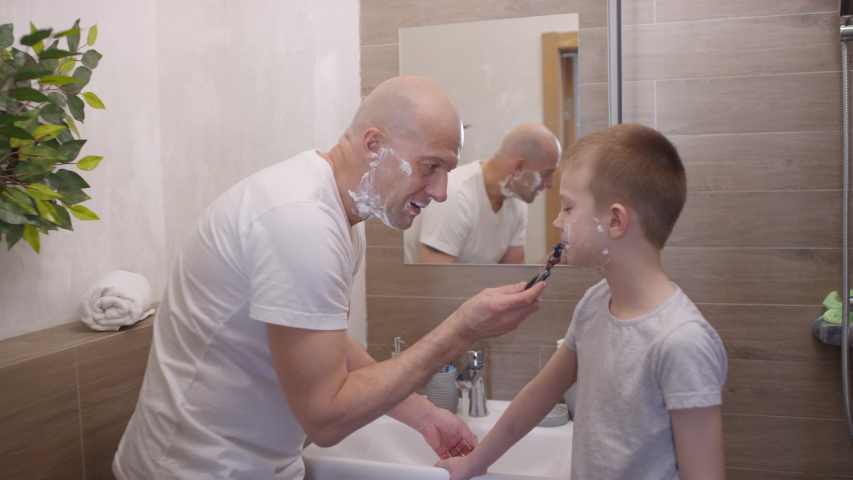 Handheld shot of bald man with shaving foam on his chin using razor and shaving 8 year old boy in bathroom | Shutterstock HD Video #1052913812