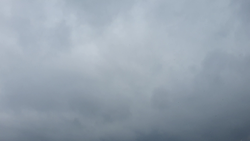 Rain drops on a background of storm clouds on a blue sky background | Shutterstock HD Video #1052913962