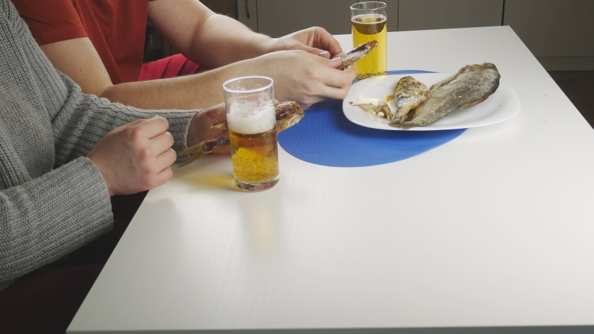 Couple drinking beer with dried fish.Sitting at the table.Tears off pieces from the carcass.The use of alcoholic beverages.Intoxicated,yellow liquid with foam in a transparent glass. | Shutterstock HD Video #1052915861