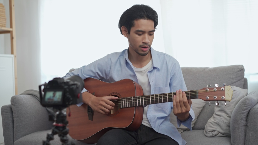 Male vlog influencer performancing music show, teaching how to play guitar, streaming to internet online audience listening at home. Man sing a song with smile face. Home entertainer, blogger concept.