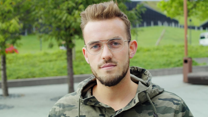 Portrait of young man with glasses looking at camera. Shot with RED helium camera in 8K | Shutterstock HD Video #1052917136