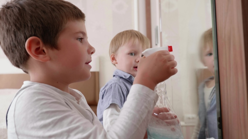Small hardworking male children help caretakers with cleaning house and wipe mirror from dirt with a detergent and a cloth, help to parents | Shutterstock HD Video #1052917283