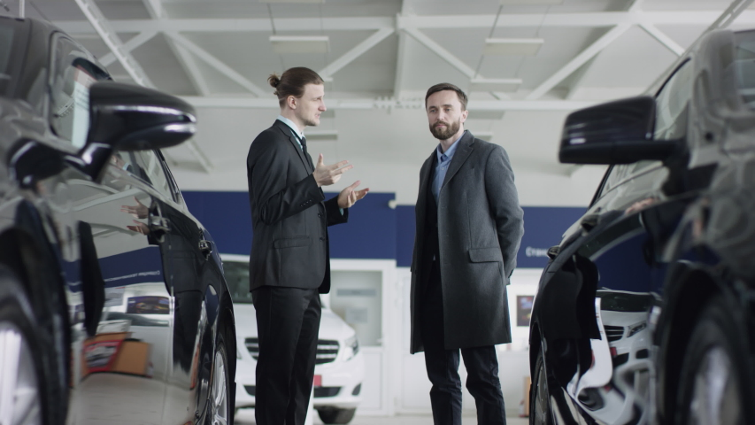 Auto dealer is working with his customer at the dealership showing a new automobile. Handsome man is talking to the car dealer choosing auto