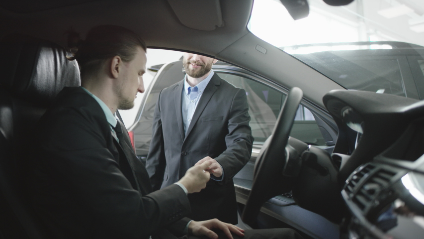 Auto dealer is telling about details in a new car and gives keys. Right sight view of handsome man sitting in the car on a driver's seat. Businessman talking while sitting in a car.