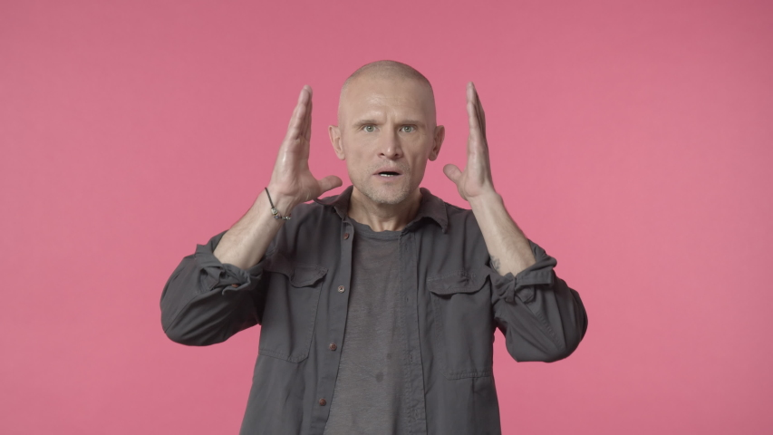 Shocked elderly bald man reacting startled and anxious, hold hands on head and nervously staring camera something bad, witness accident, distressed with concerning awful situation, pink background