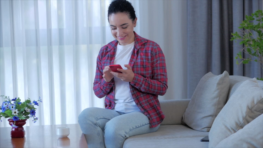 Relaxed Woman using smart phone typing on phone sitting on sofa at home, businesswoman sits at home types on smartphone checks mail to study online work at home. Royalty-Free Stock Footage #1052918879