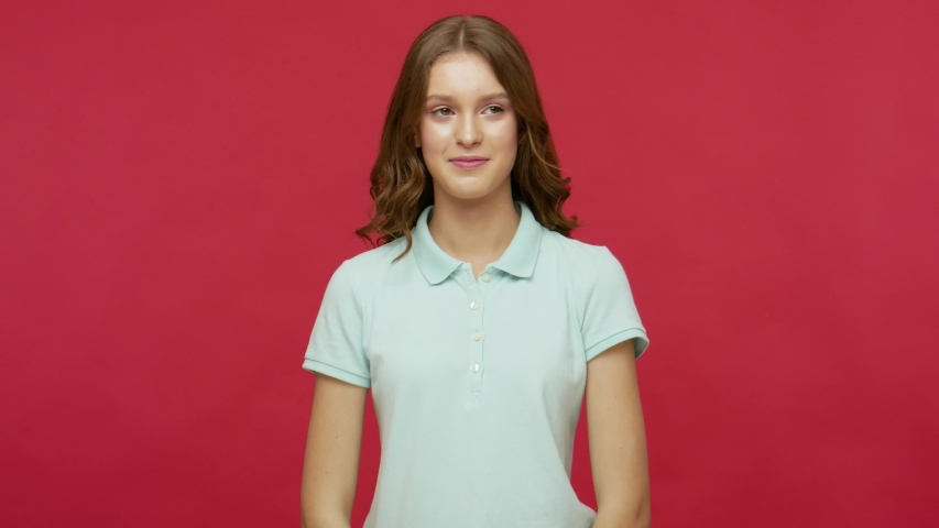 Bad manners. Impolite young brunette woman in polo t-shirt furtively picking her nose, pulling out boogers with comical humorous funny face expression. indoor studio shot isolated on red background