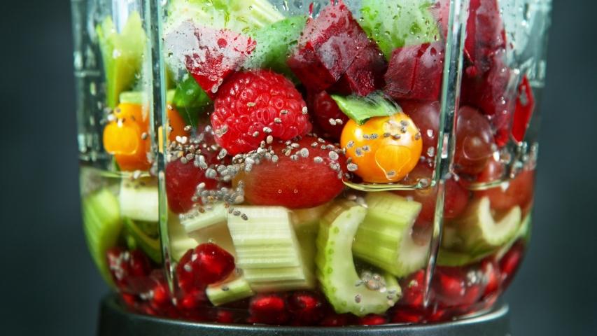 Fresh fruit and vegetables smoothie blended in blender, back view. Healthy eating concept. Super slow motion filmed on high speed cinematic camera.