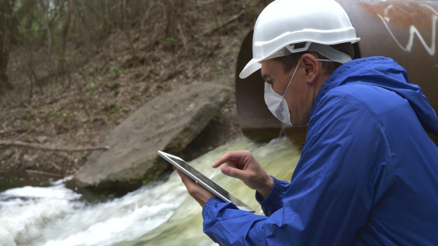 Environmental engineer in protective mask. Pollution of the environment and soil of the planet. Environmental engineer checks waste water. Environmental pollution of planet. Wastewater soil pollution.