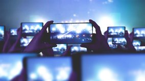 Fans are recording videos on smartphones. A lot of smartphones. Musical concept. Live Stream. Stories. The crowd watches a concert, sings, jumps. Strobing stage lights. Happy people at the concert.