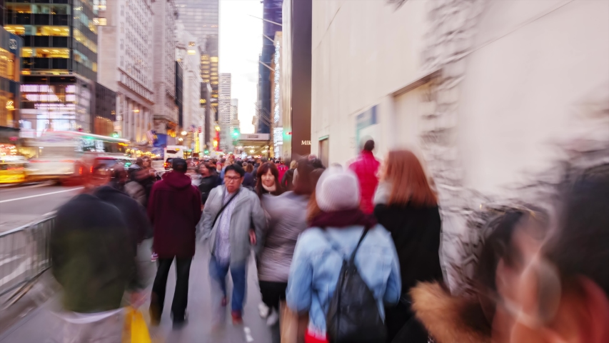 NEW YORK CITY - NOVEMBER 2016: Hyperlapse walk through crowd of people on Fifth Avenue and 57th street at dusk time in New York City, NY, USA