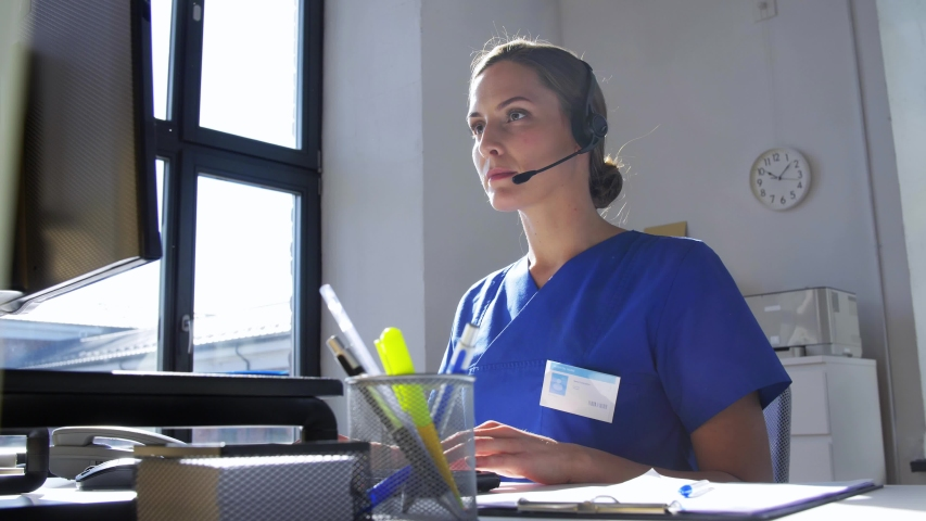 Medicine, technology and healthcare concept - female doctor or nurse with headset and computer working at hospital | Shutterstock HD Video #1052930018
