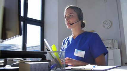 medicine, technology and healthcare concept - female doctor or nurse with headset and computer working at hospital