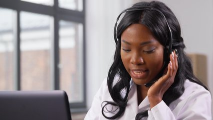 medicine, online service and healthcare concept - african american female doctor or nurse with headset and laptop having conference or video call at hospital